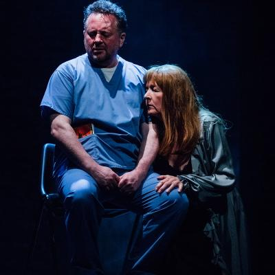Lady crouched down next to male nurse on chair in Clear White Light