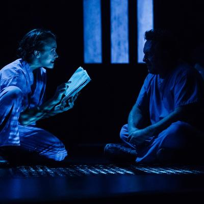 Young female nurse reading from book to older male nurse in dark in Clear White Light
