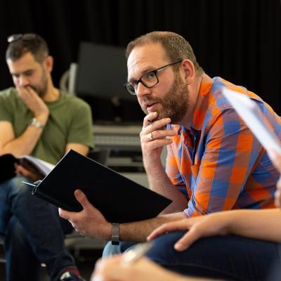 Three men sitting reading