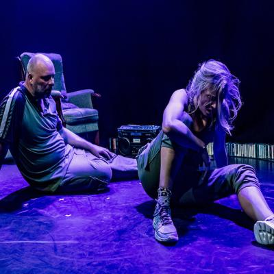 Man and woman on sitting on stage both looking down