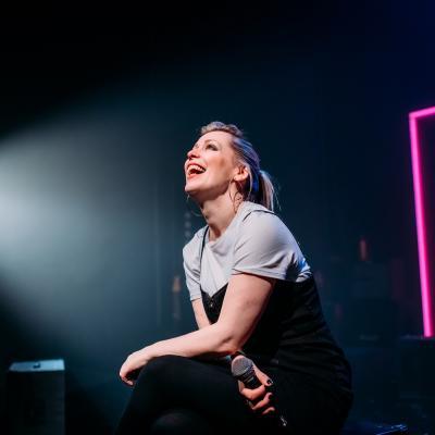 Female on stage under spotlight