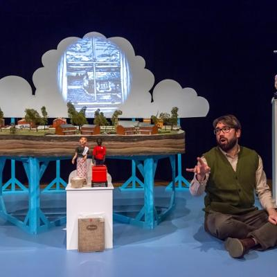 Man kneeling next to miniature town model and doll characters