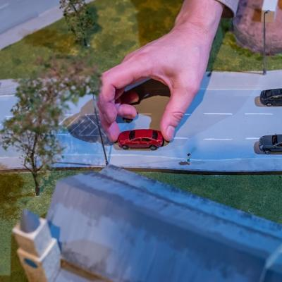 Hand moving car on miniature town road model set