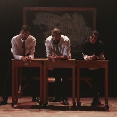 Three pupils in uniform leading over wooden desks