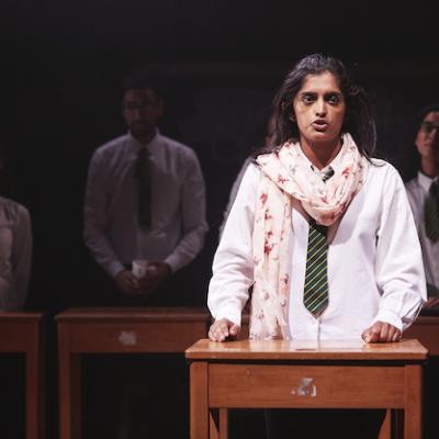 Young woman in school uniform stood behind wooden desk