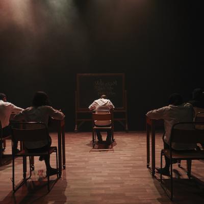 Five pupils in uniform sat behind wooden desks looking at blackboard