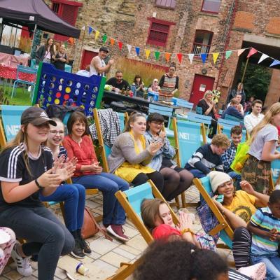 People on deckchairs enjoying performance
