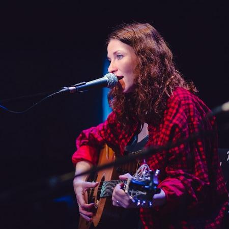 Rosie Doonan singing at microphone and playing guitar