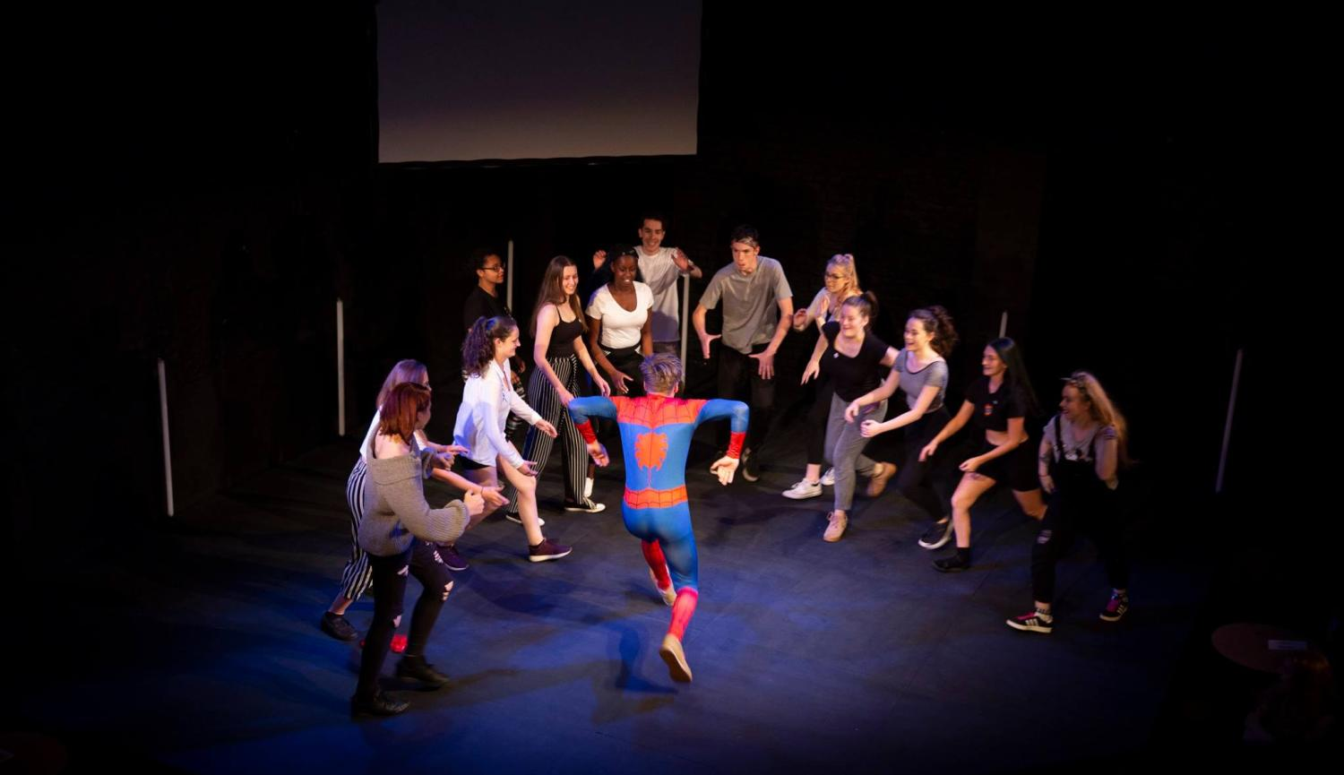 Young People in a circle and young person in spiderman costume
