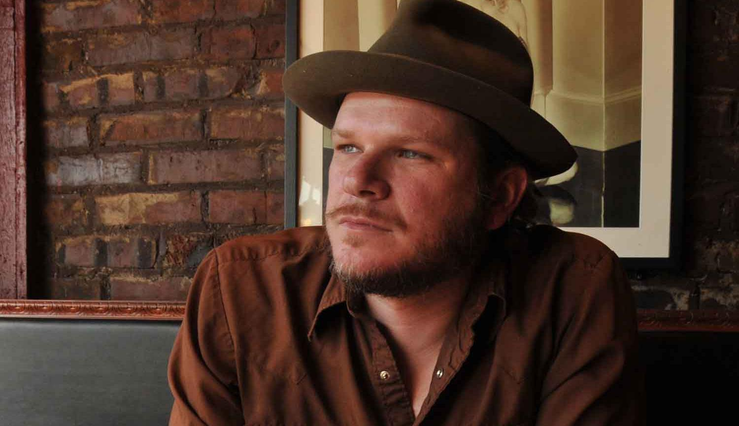 Image of Jason Eady sitting at table wearing hat