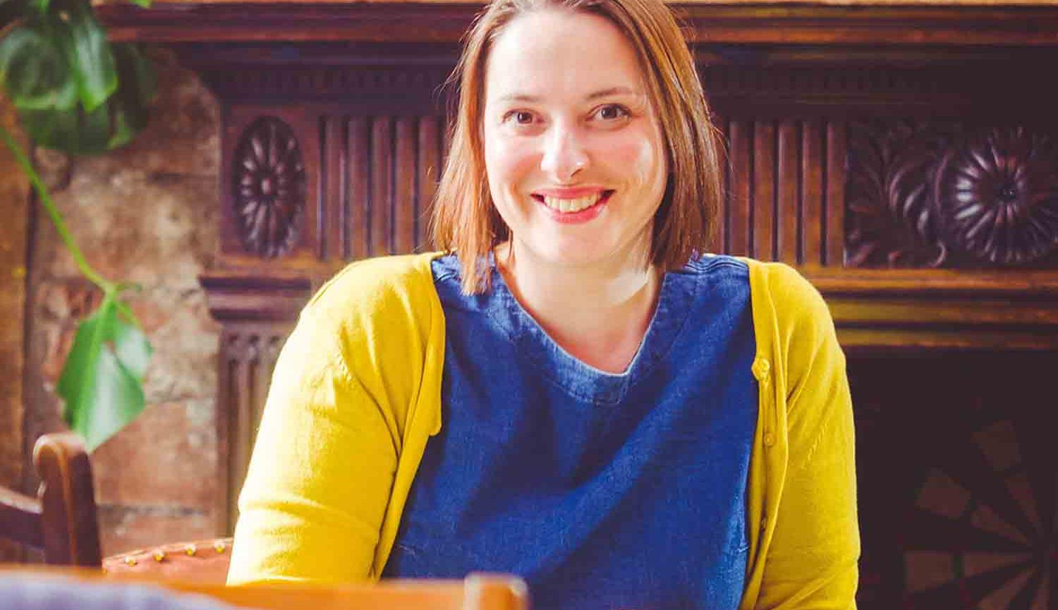 Photo of a woman sitting on a chair wearing a yellow cardigan and a blue top in front of a mantlepiece