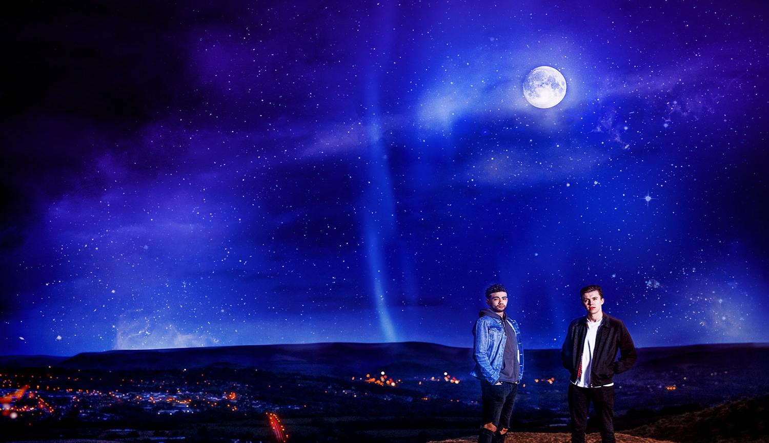 Two men on hilliside at night with moon overhead