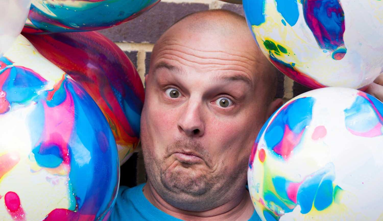 Jesterval Lee Kyle Family Show image of mans face surrounded by beach balls