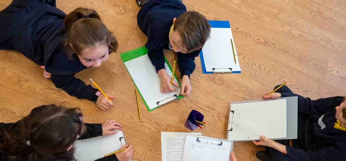 Group of children lying on floor writing on paper on clipboards