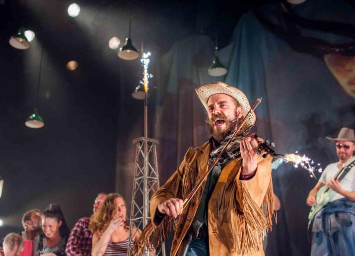 Photo of man with hat playing fiddle and singing on stage with other musicians in background