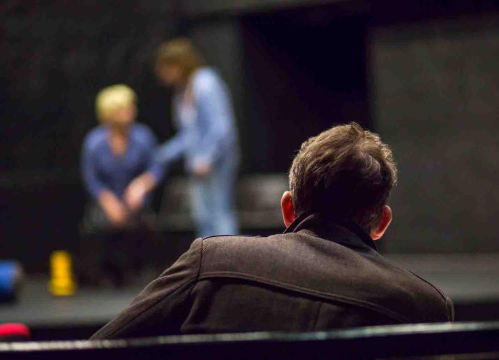 Photo of back of mans head and shoulders sitting watching two people on stage