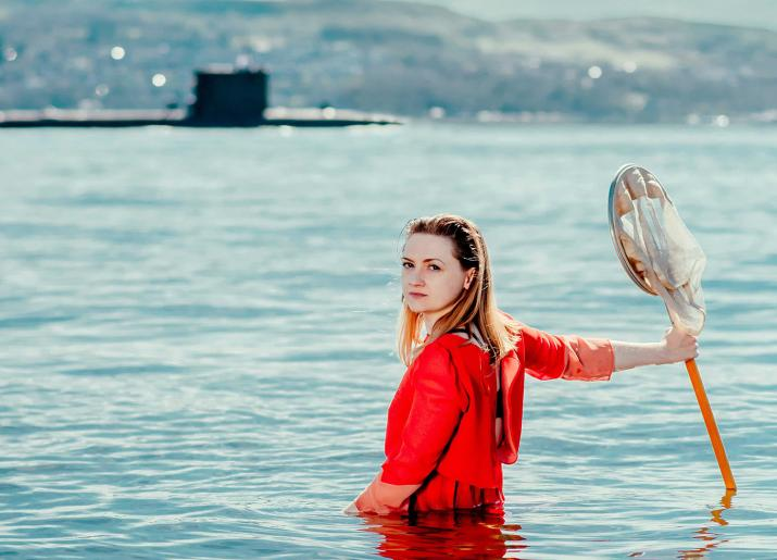 Woman in water in front of submarine
