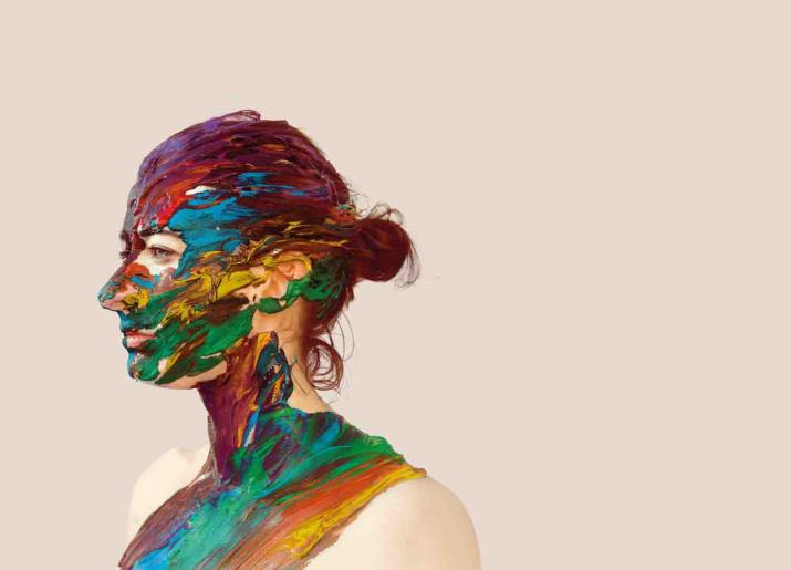 Photo of head and shoulders of woman standing side on to camera with lots of different colours of paint on her skin and hair