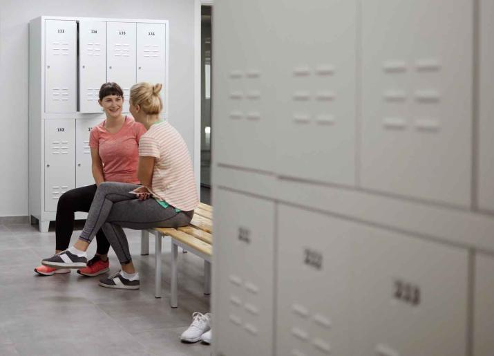 Photo of two women sitting  talking on bench in changing room with lockers around them