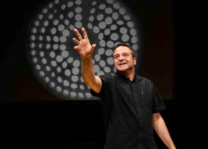 Man standing pointing forward with his right hand in front of a black screen with a white  circle design on it