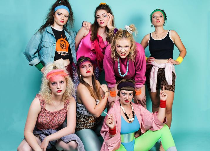 7 women dressed in 80s workout gear grimace at the camera