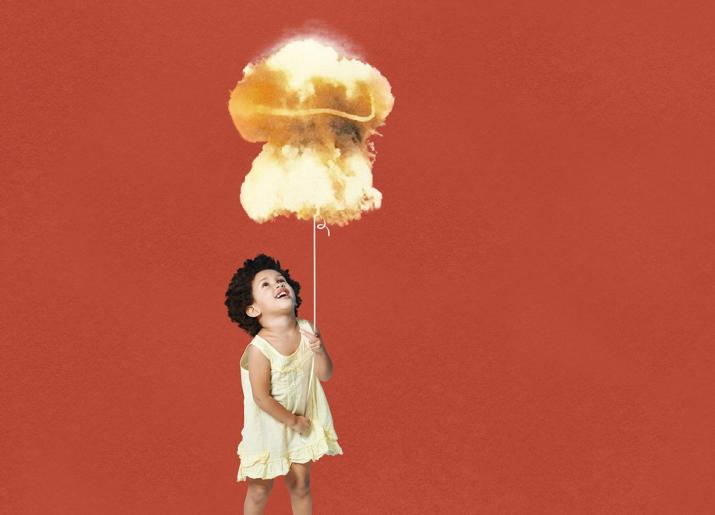 Small girl in dress holding string of a balloon in the shape of a nuclear mushroom cloud