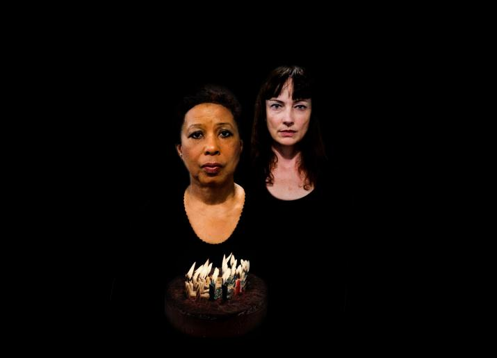 two women standing in the dark/black background