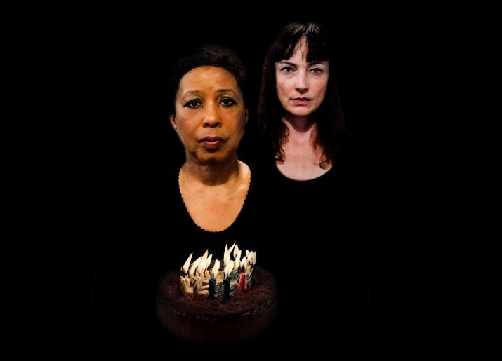 Two women in black one holding a birthday cake with lit candles