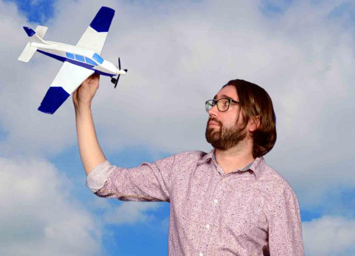 Man holding model airplane in the air