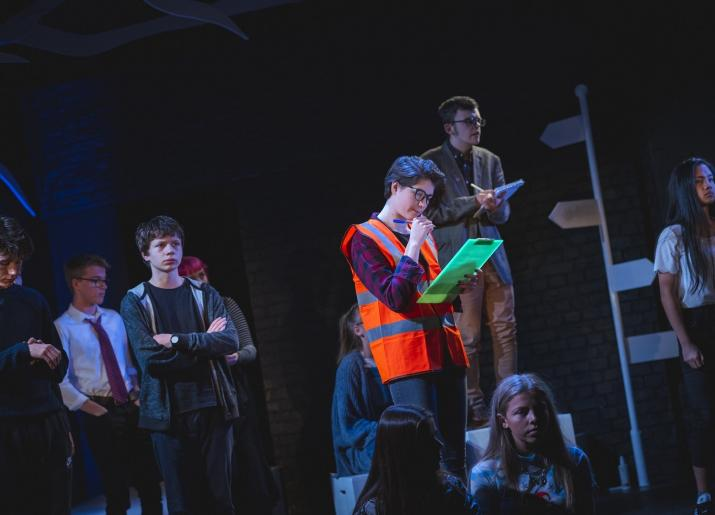 Photo of actors on stage with one wearing a high vis vest and holding a clipboard